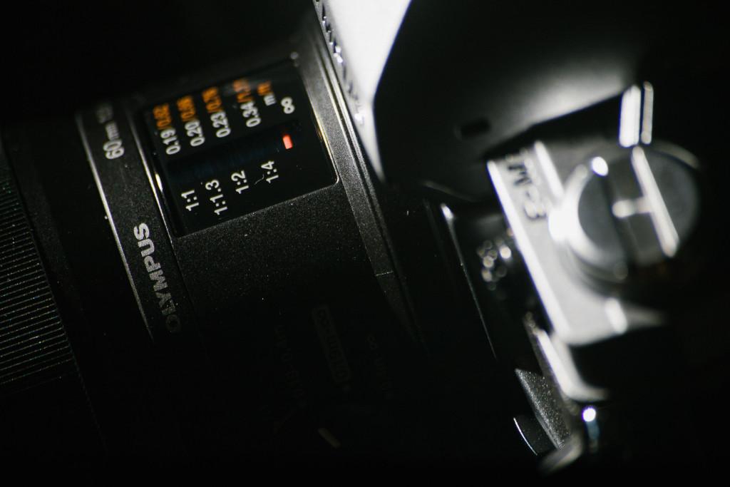 Entfernungsanzeige am 60mm f/2.8 Makro. Ein kleiner roter Strich, der an die Frequenzeinstellung alter Radios erinnert, zeigt die Entfernung an.