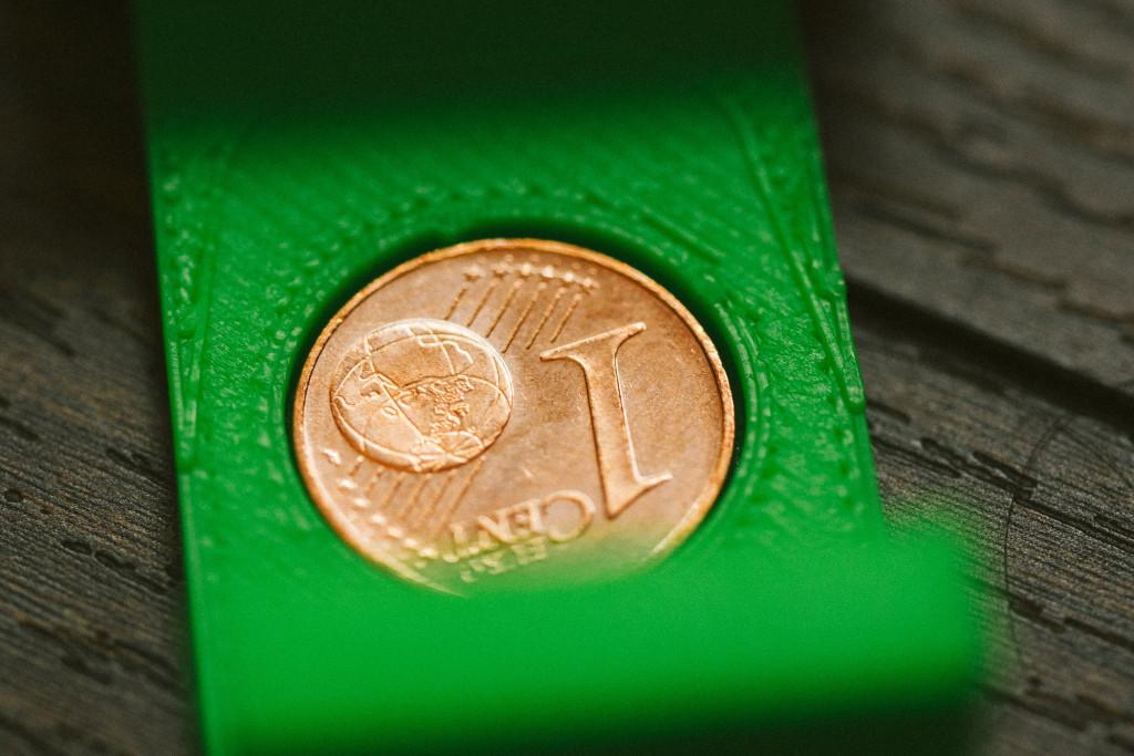 Schutzkappe für E-M1 Akkus – Ein Cent-Stück markiert einen geladenen Akku