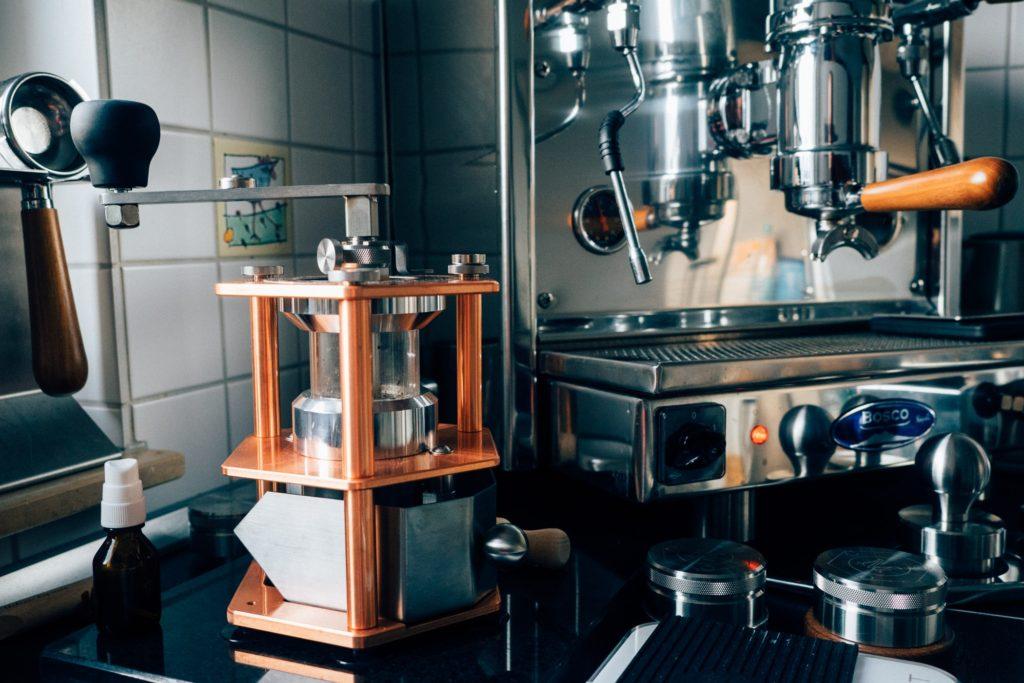 Handmühle Mahlgut 1 in der Kupfterausführung vor der Bosco Handhebelmaschine