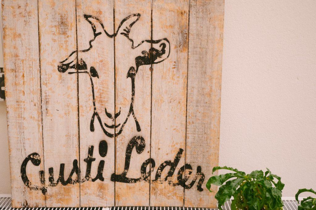 Holzschild mit Firmenlogo von Gusti-Leder