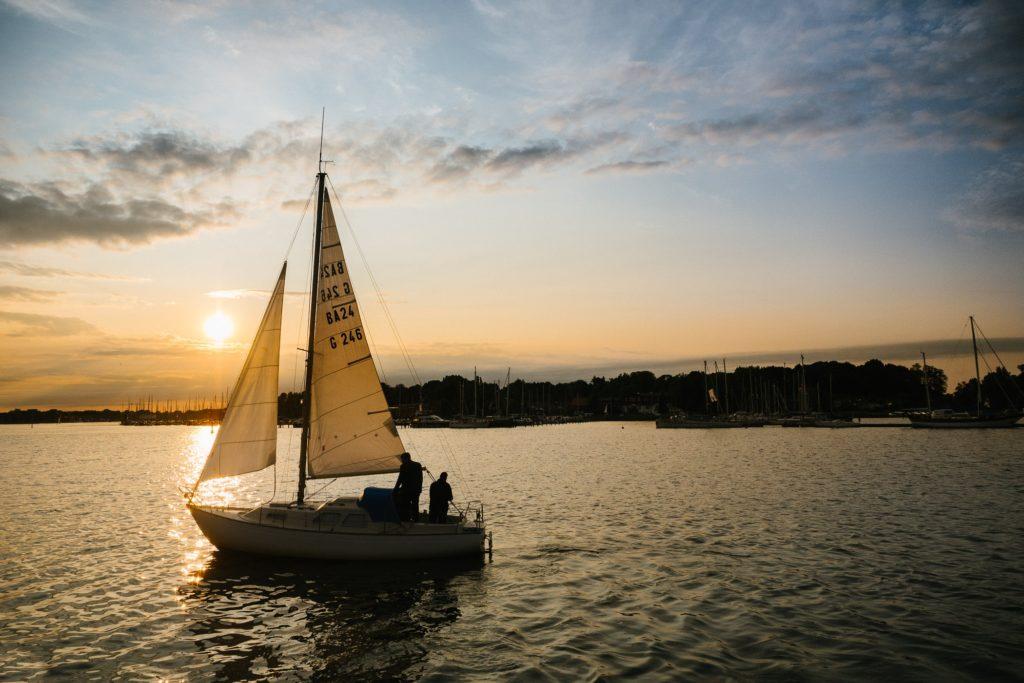 Segelboot im Sonnenuntergang im Hafen von Rostock