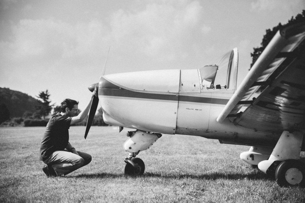 Bernd Sieker hockt vor dem Propeller des Flugzeugs und prüft die Maschine